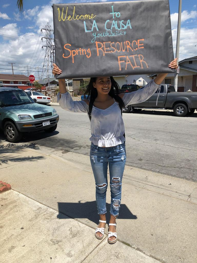 LA CAUSA student holds a sign for their Spring Resource Fair