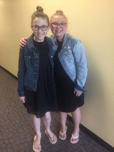 two girls in jean jackets and glasses smile