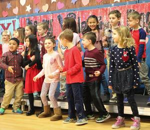 Photo of Washington School 1st graders as they perform a Valentine's Day singalong for family members.