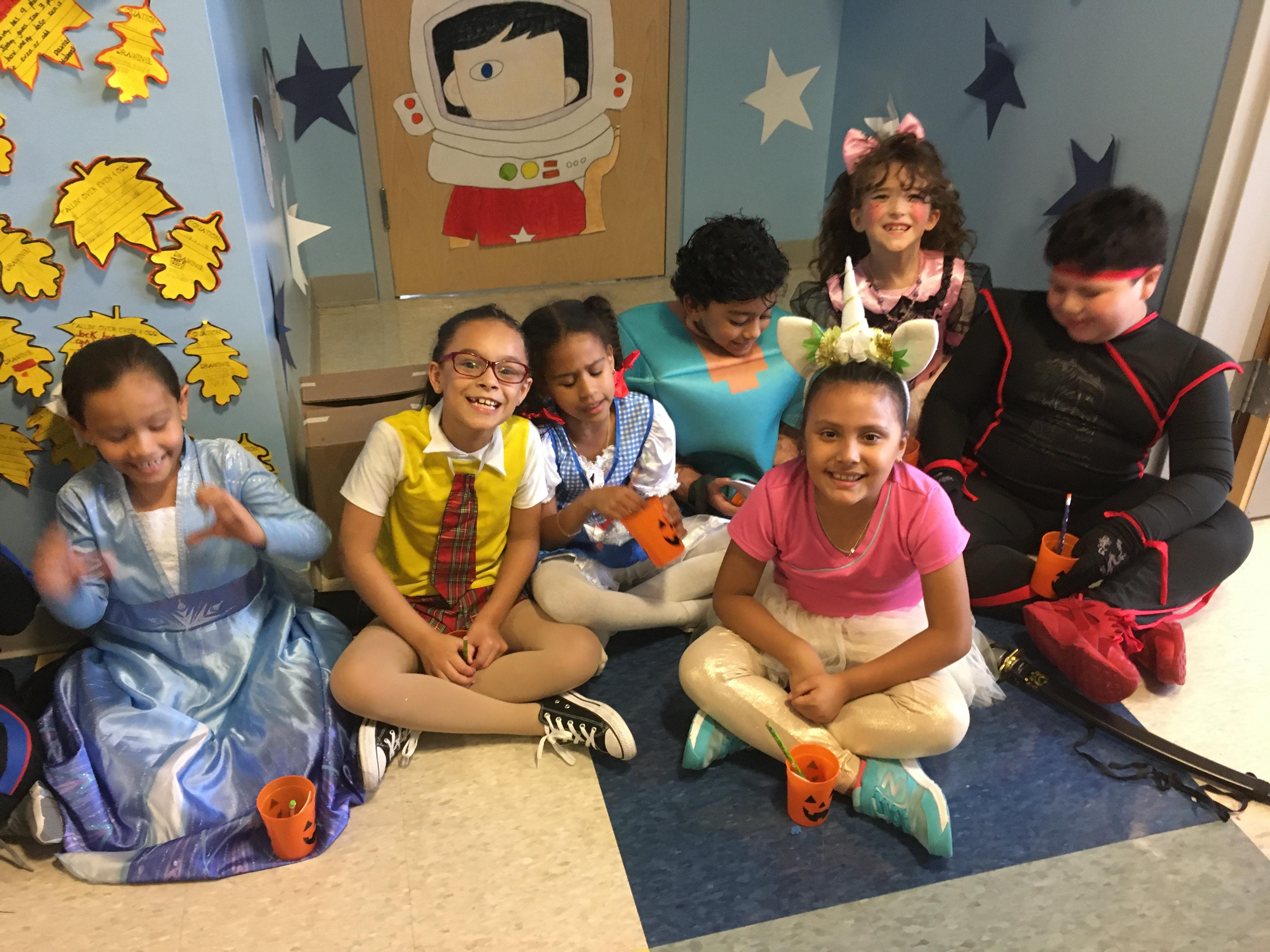group of kids sitting on hallway floor in their costumes