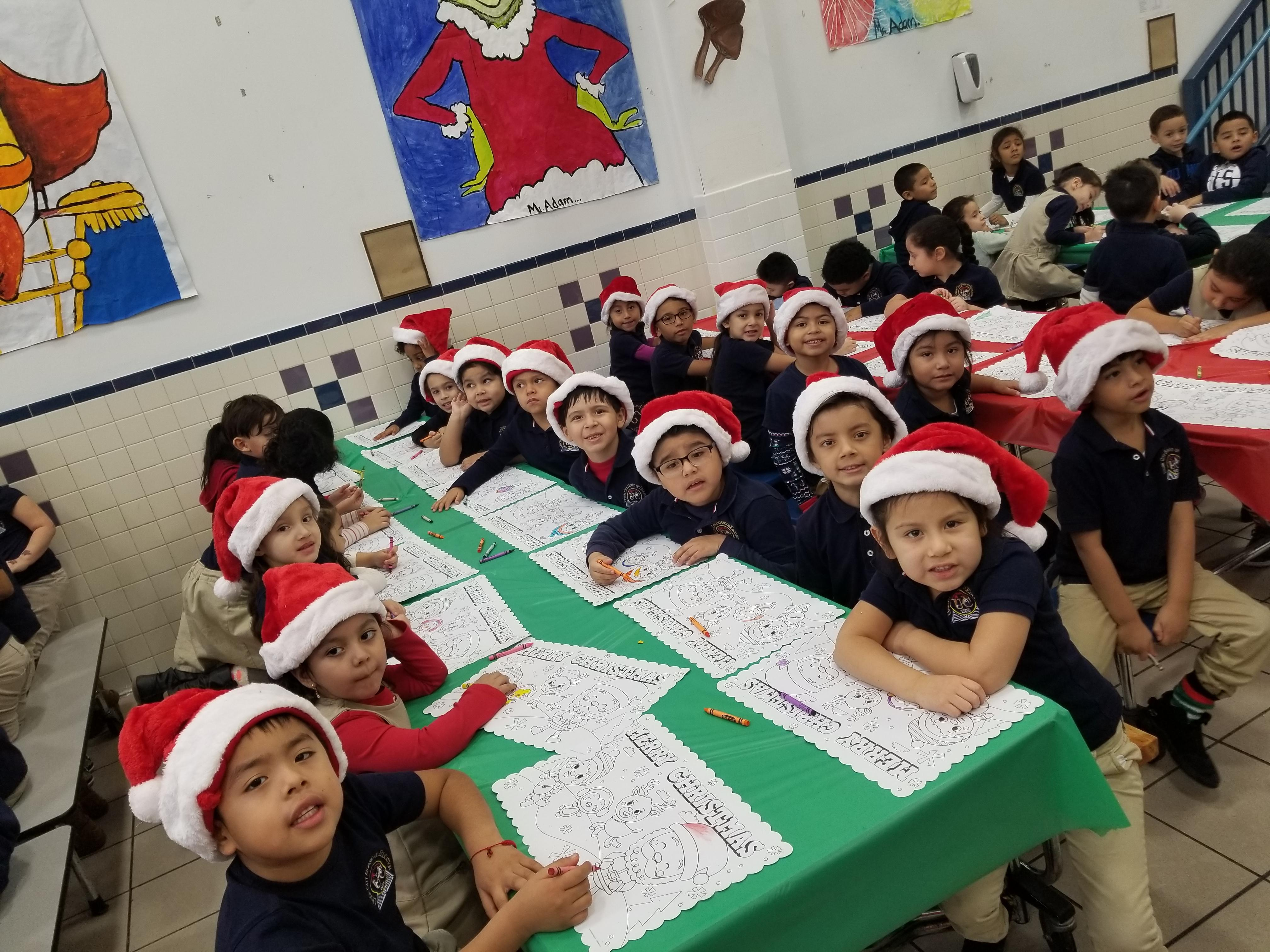 children with santa hats sitting at the tables coloring