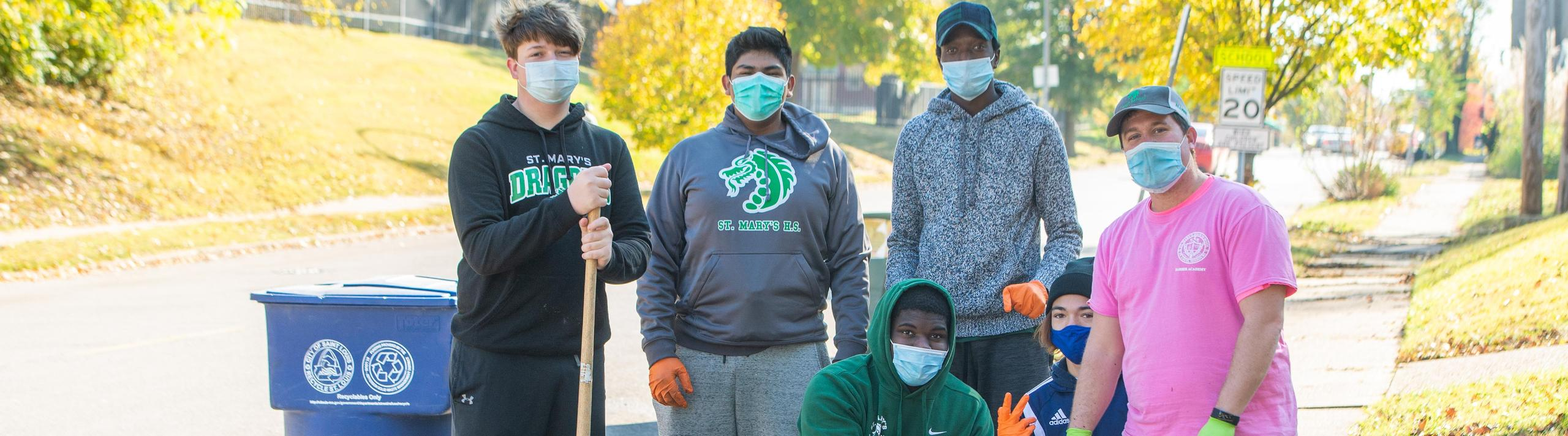 Members of the Barber Academy working together to clean up streets in South City.