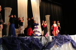 teachers in flamenco costume dancing along with the two musicians one with a guitar and the other the mambo drum