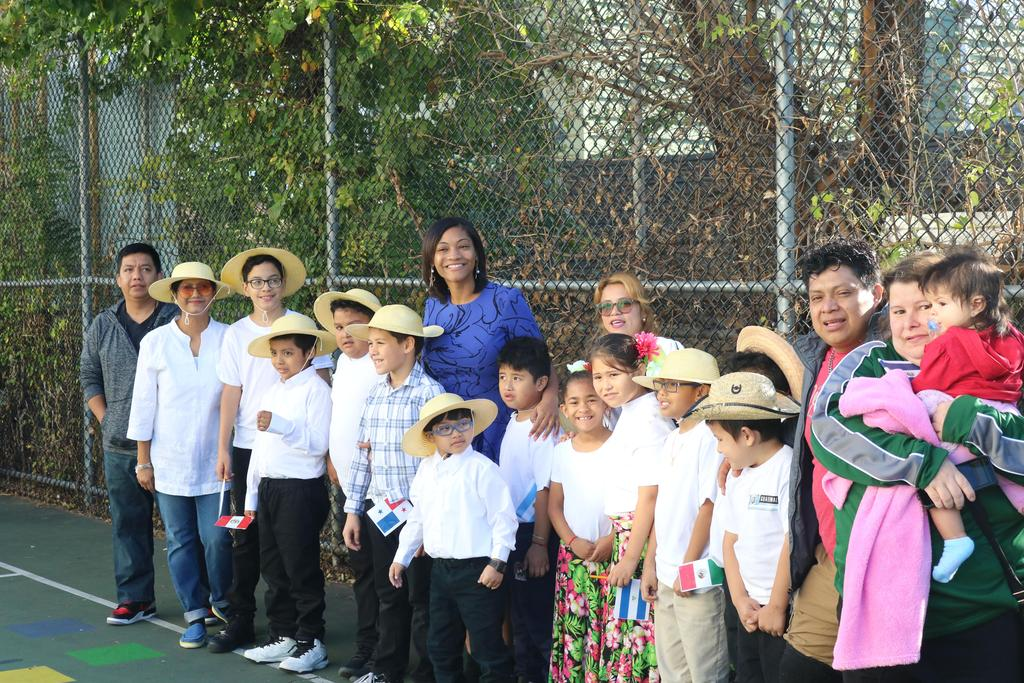 Mrs. Bristol with two aides and her class standing by the school yard fence