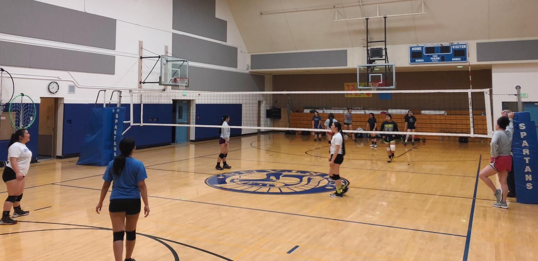 volley ball team at practice in the school gym