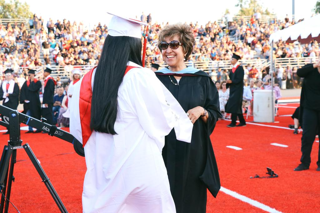Chief Academic Officer Maribel Mattox shakes a graduate's hand