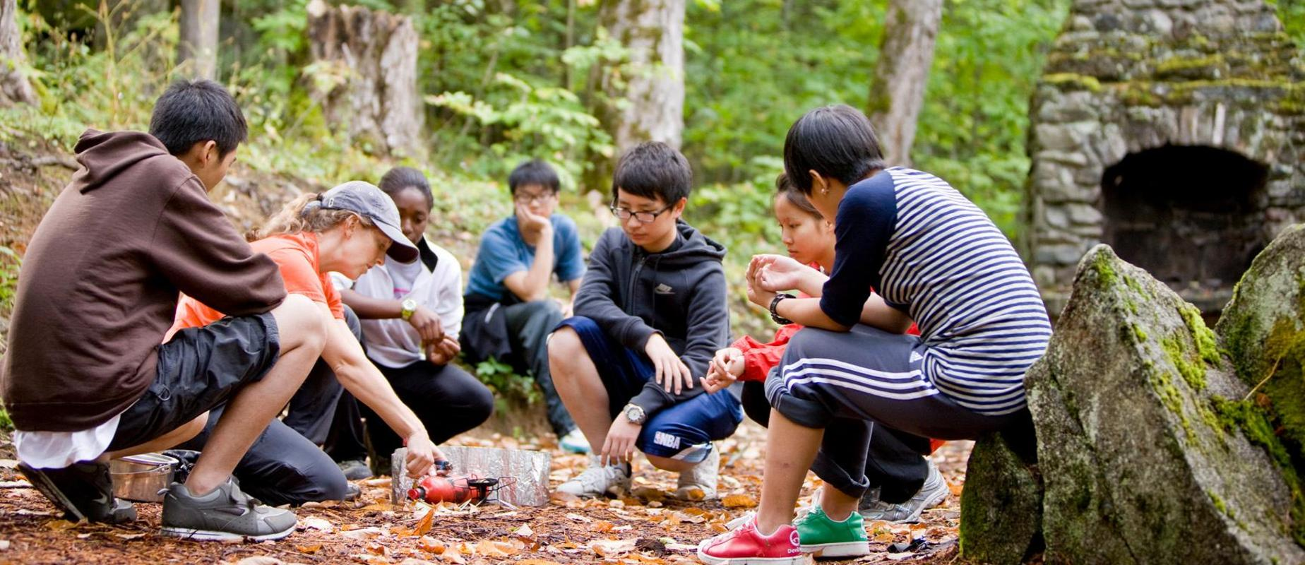 A faculty member shows students how to start a campfire.