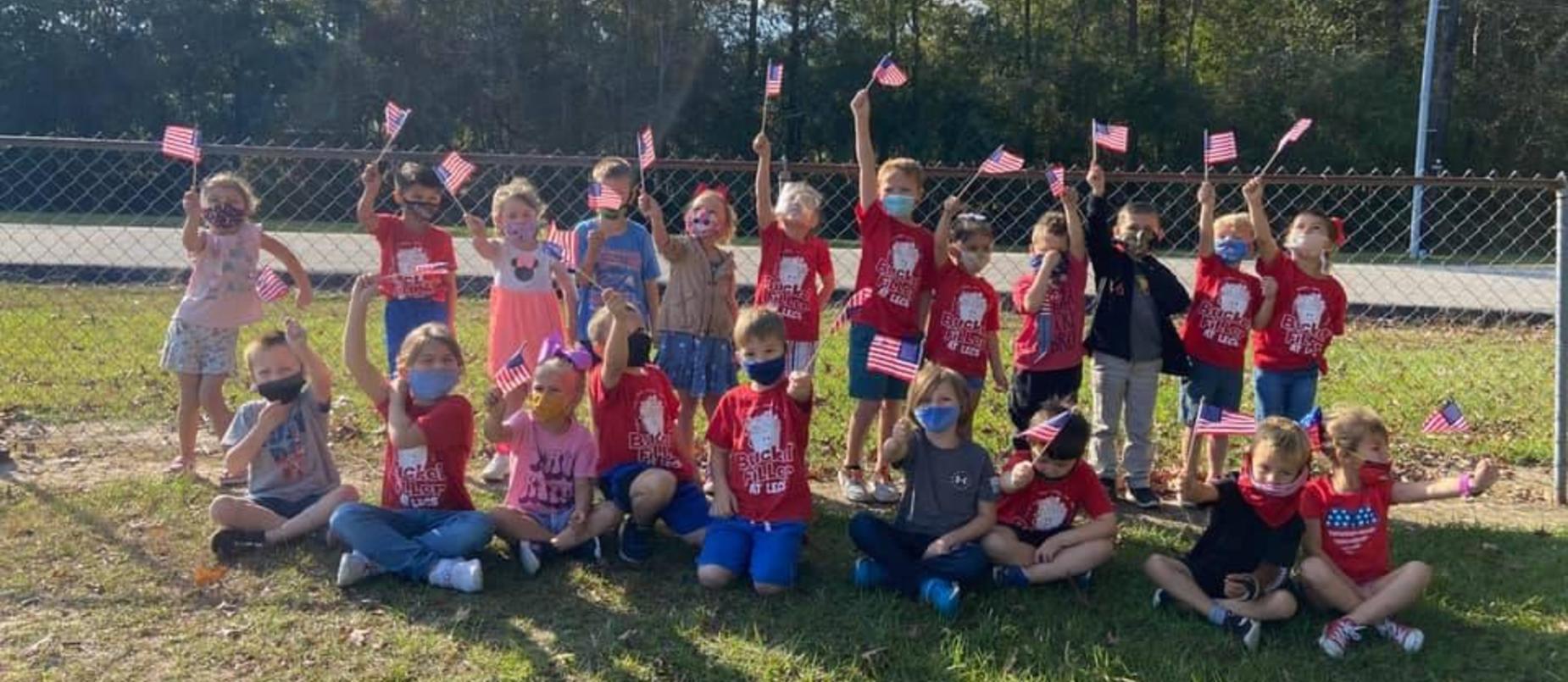 Early Childhood students waving US flag