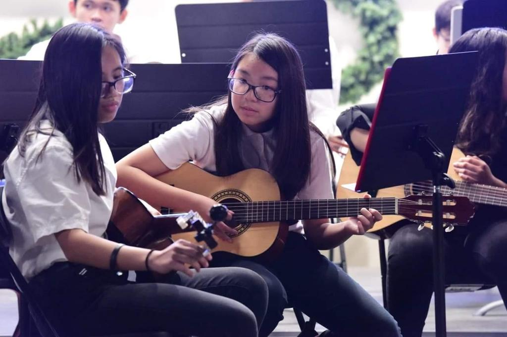 Two students tuning their guitars at the Winter Concert, 2018.