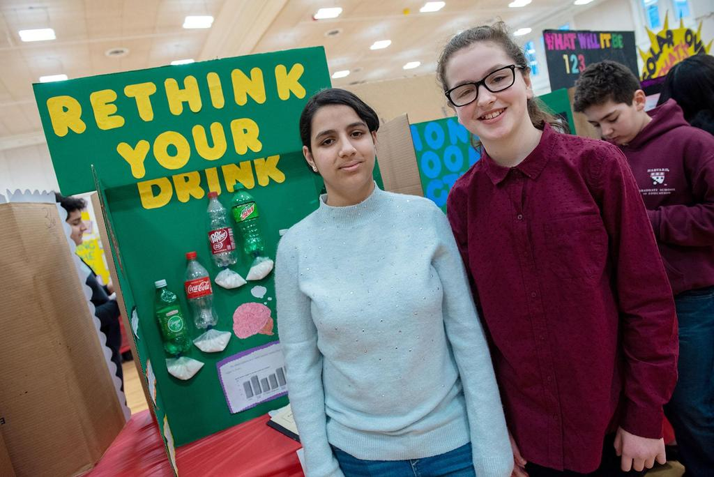 Two students stand in front of their science fair project