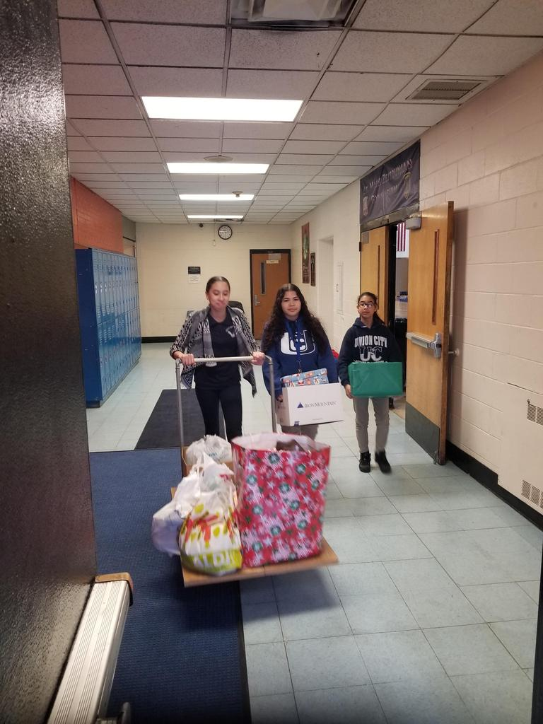 student council reps moving the clothing into bags to the truck outside