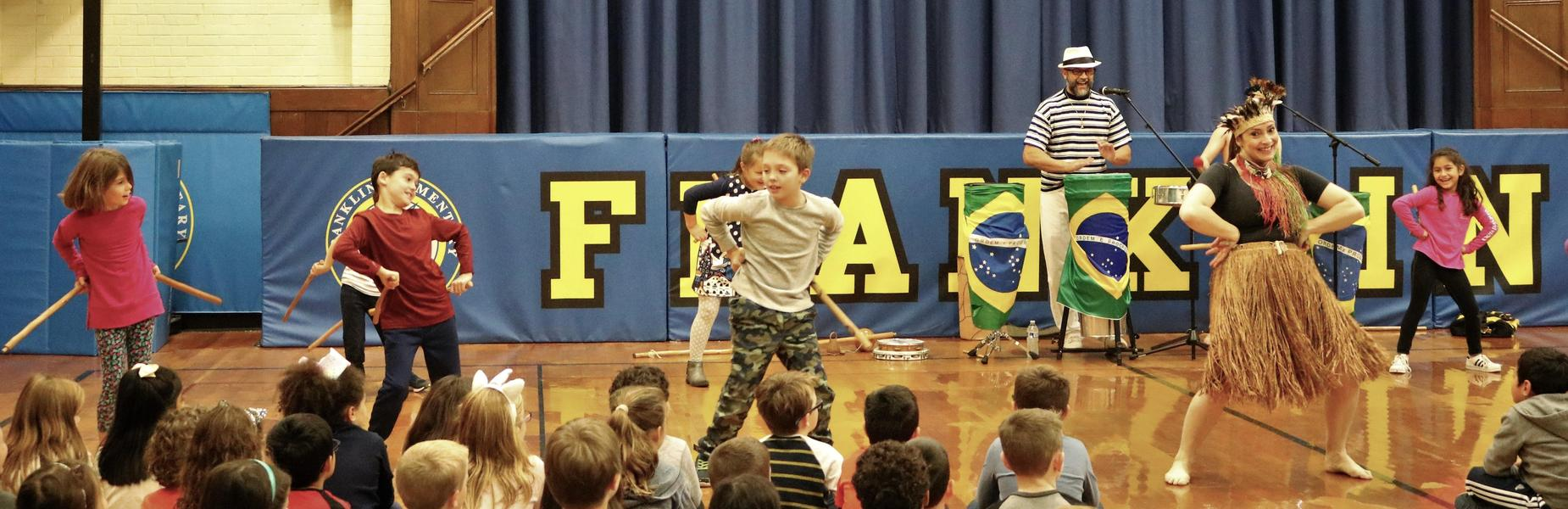Franklin School students join in a lively performance by Ginga Brasileira on Nov. 19 as students explore the history, language and culture of Brazil through music and dance.  The dancers enlisted students in performing the Maculele, a stick dance from the Brazilian sugar cane plantations, while showcasing other dances including the Capoeira which combines dance, martial arts, and music. The event is part of a cultural arts program provided by the school's Parent -Teacher Organization.