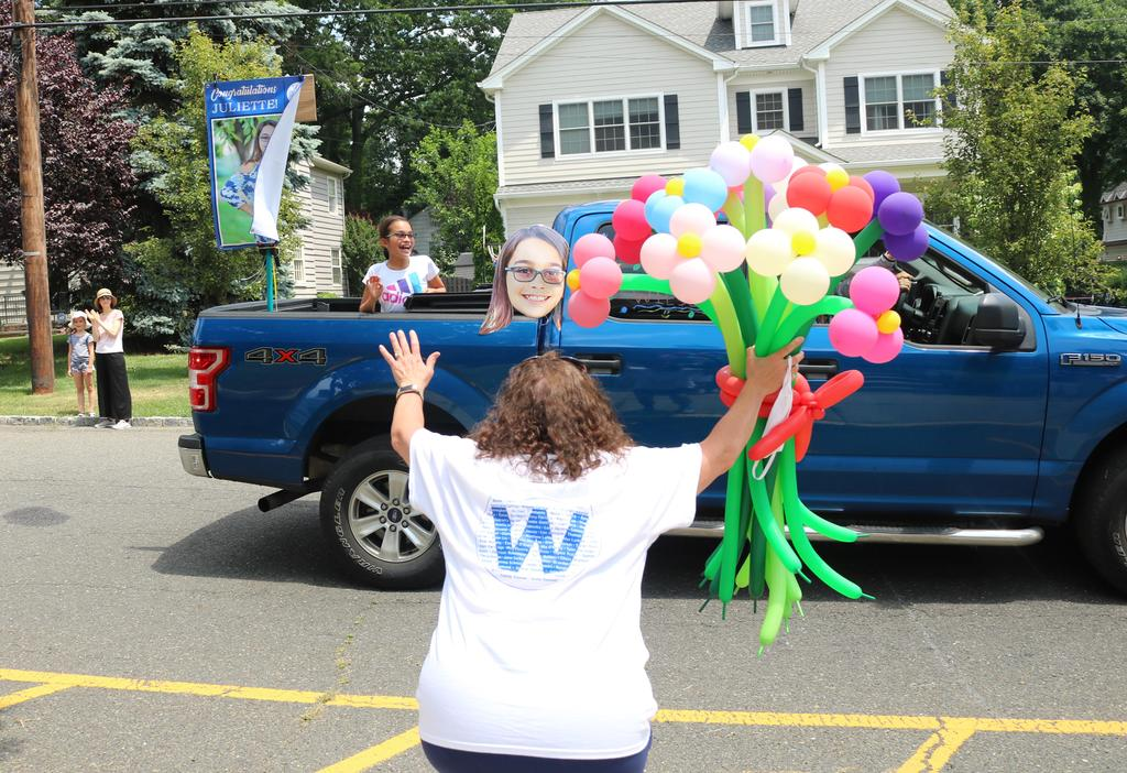 Photo of teacher with balloons enthusiastically greeting 5th grader driving by as part of Grade 5 Clap Out.