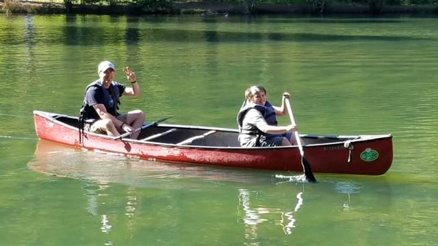 canoe on lake being rowed by teacher and student
