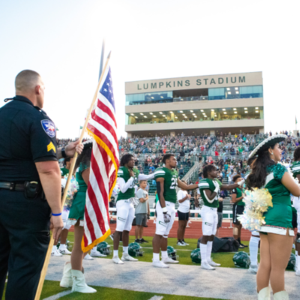 stadium during a football game with officer holding american flag, charmers, football players and fans in stands