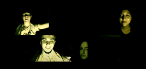 This photo depicts a moment from the attached video of four students lit up in the dark