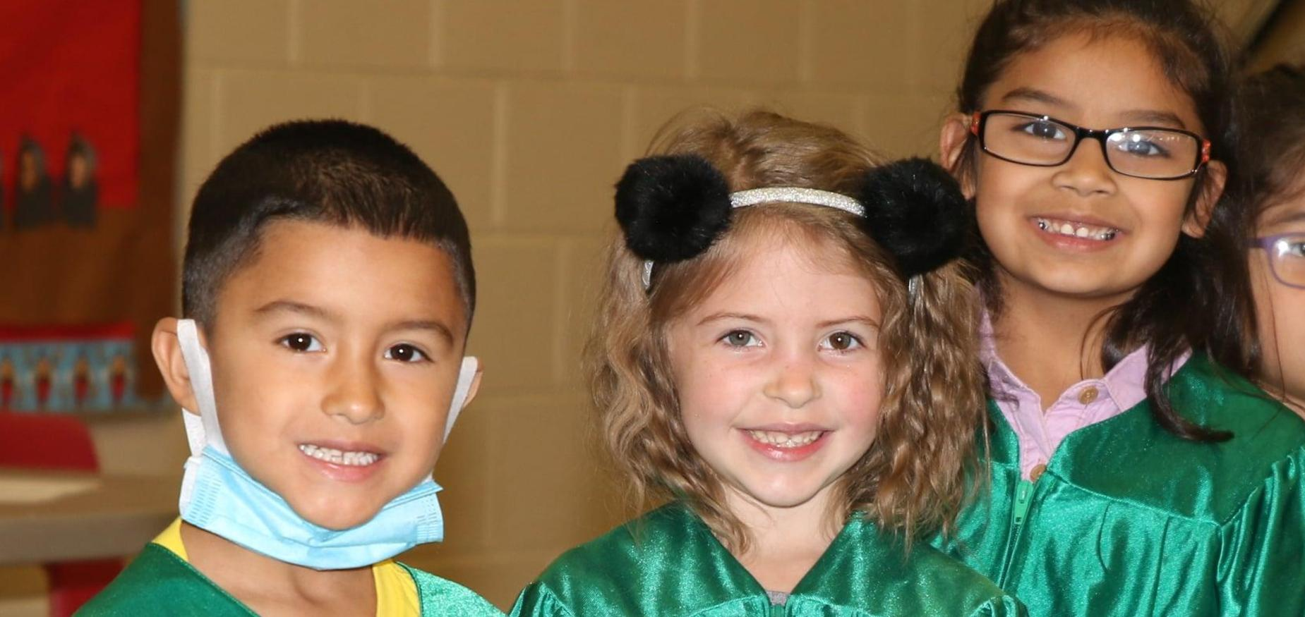 Kindergarten students get ready to take their graduation photos in caps and gowns!