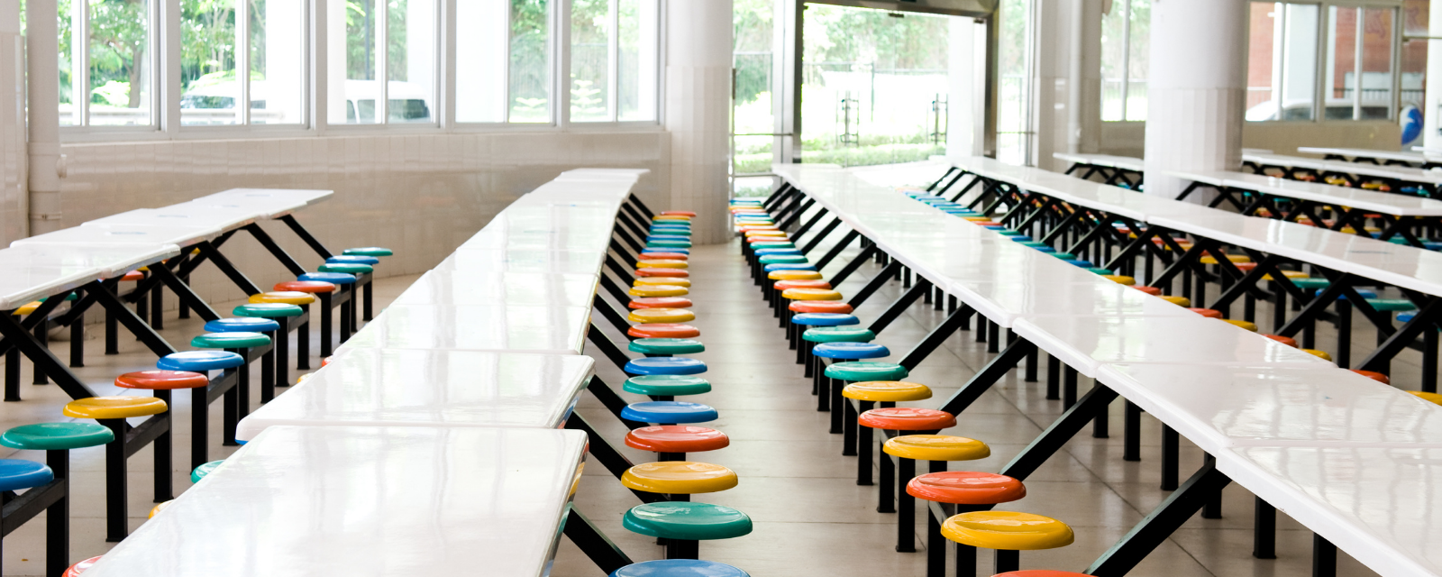 empty cafeteria tables with colorful stools