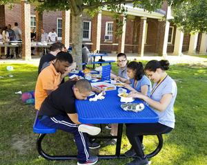 Students at a picnic table enjoying their supper.