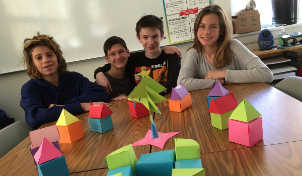 Students pose with their geometric net shapes in math class.