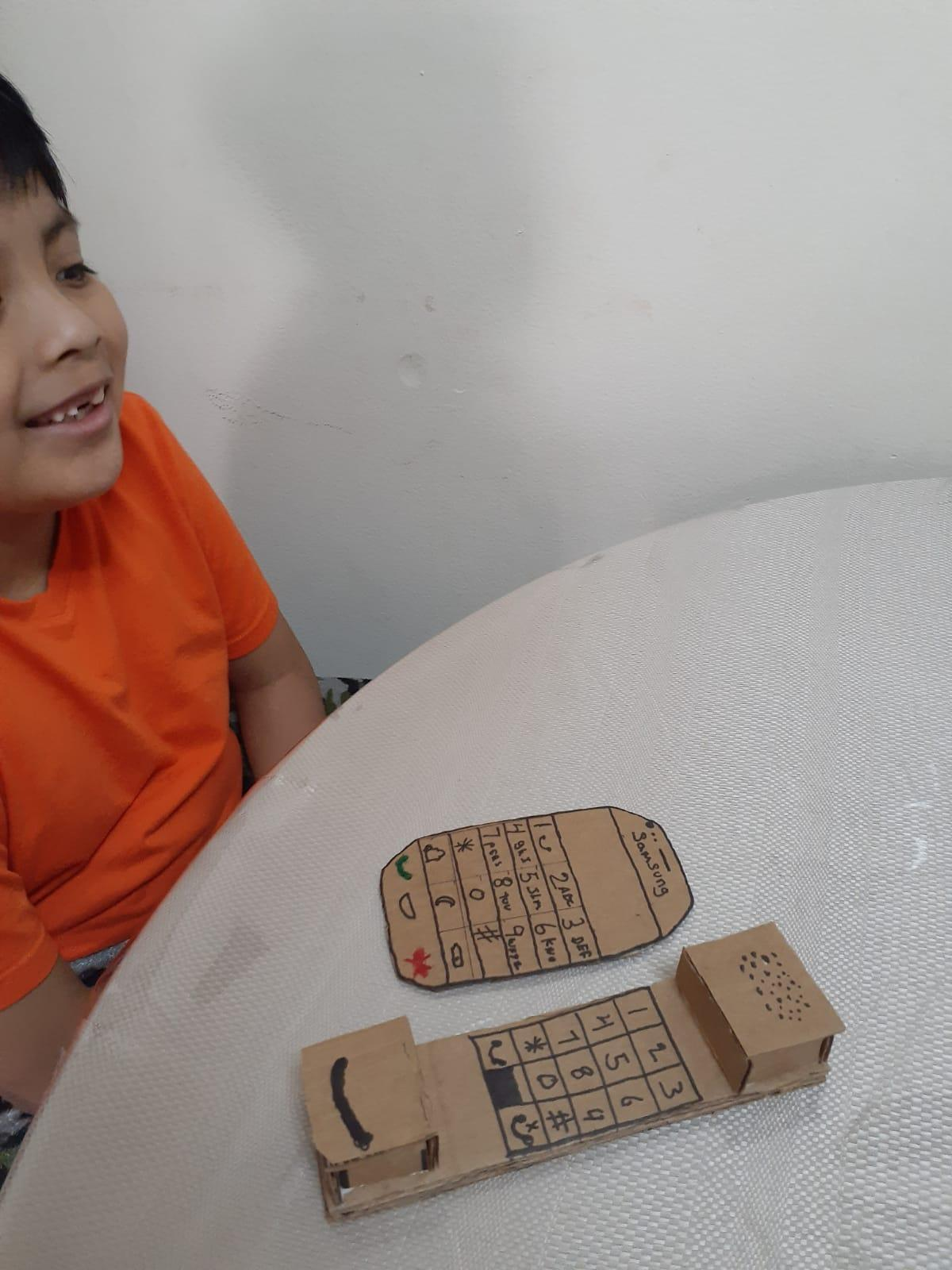 boy made a cardboard portable phone and smartphone