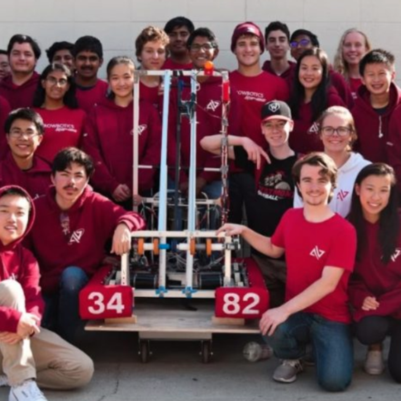 students from the Robotics club pose around their robot