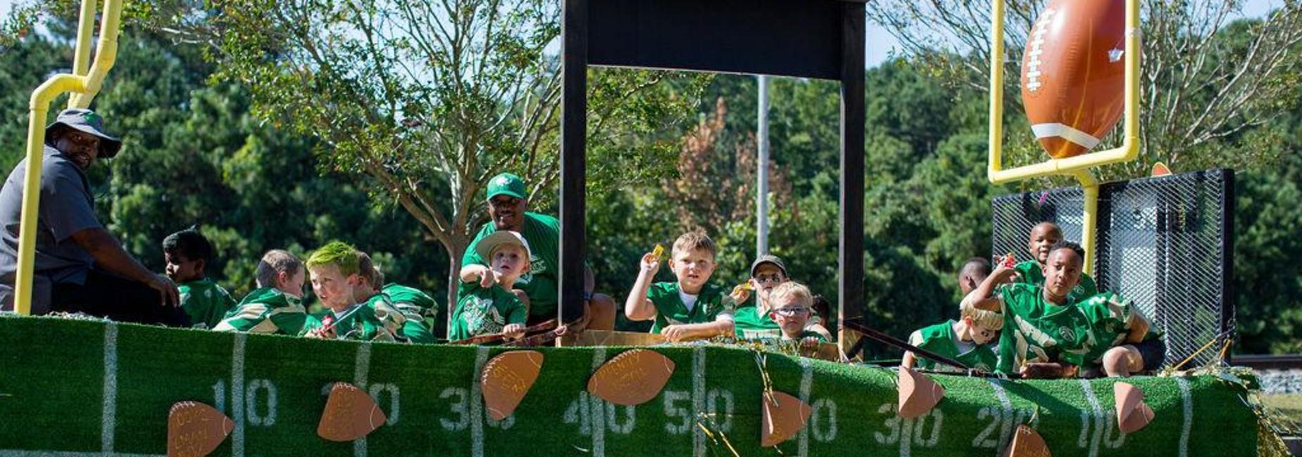 Youth Football players throwing candy from homecoming float