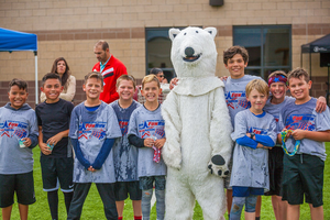 Students at Fun Run event standing with NSA mascot - Polaris the Polar Bear.
