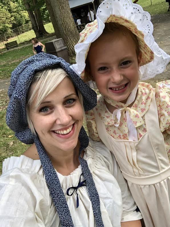 Smiling student and teacher dressed in Pioneer clothing.