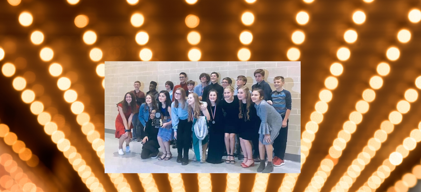 large group of theatre students pose together with the awards they earned at competition