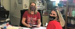 Two female South School staff members in red shirts wearing masks.  One is drawing and one is cutting with scissors.