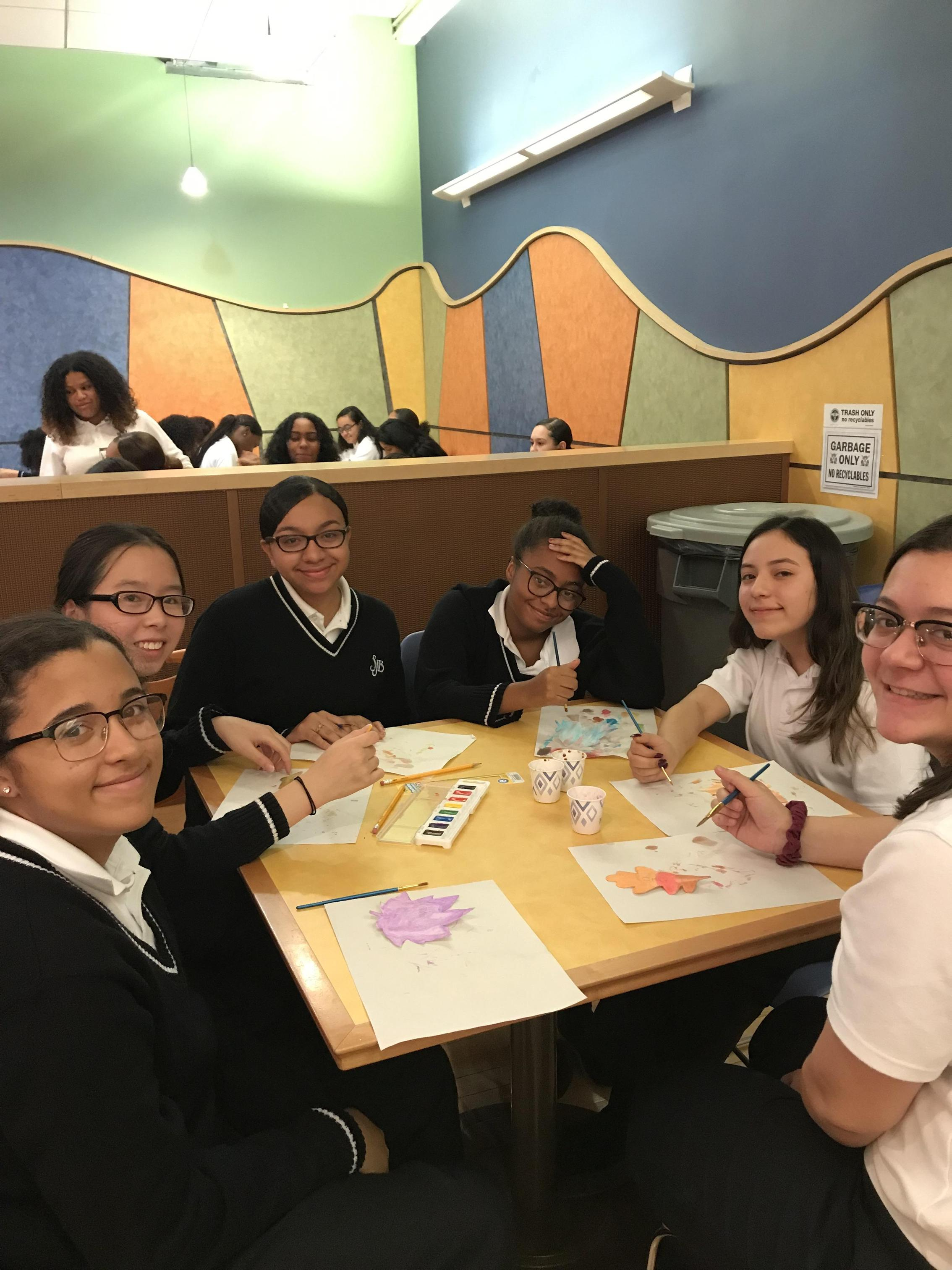 Six girls sit at table with art supplies