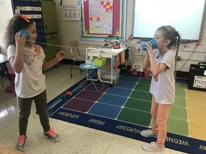 Students experiment with sound using cups and string.