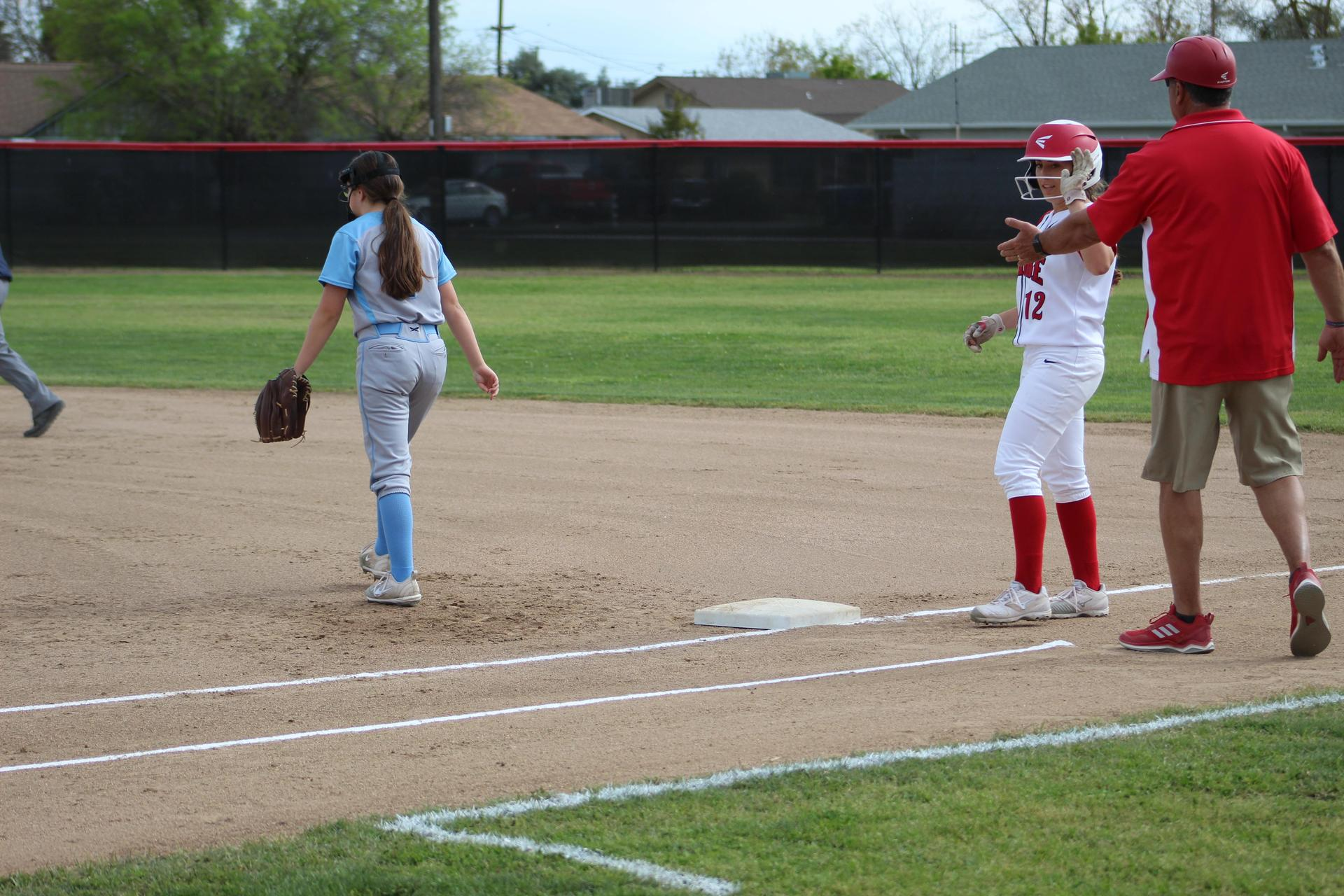 Varsity girls playing softball against Yosemite