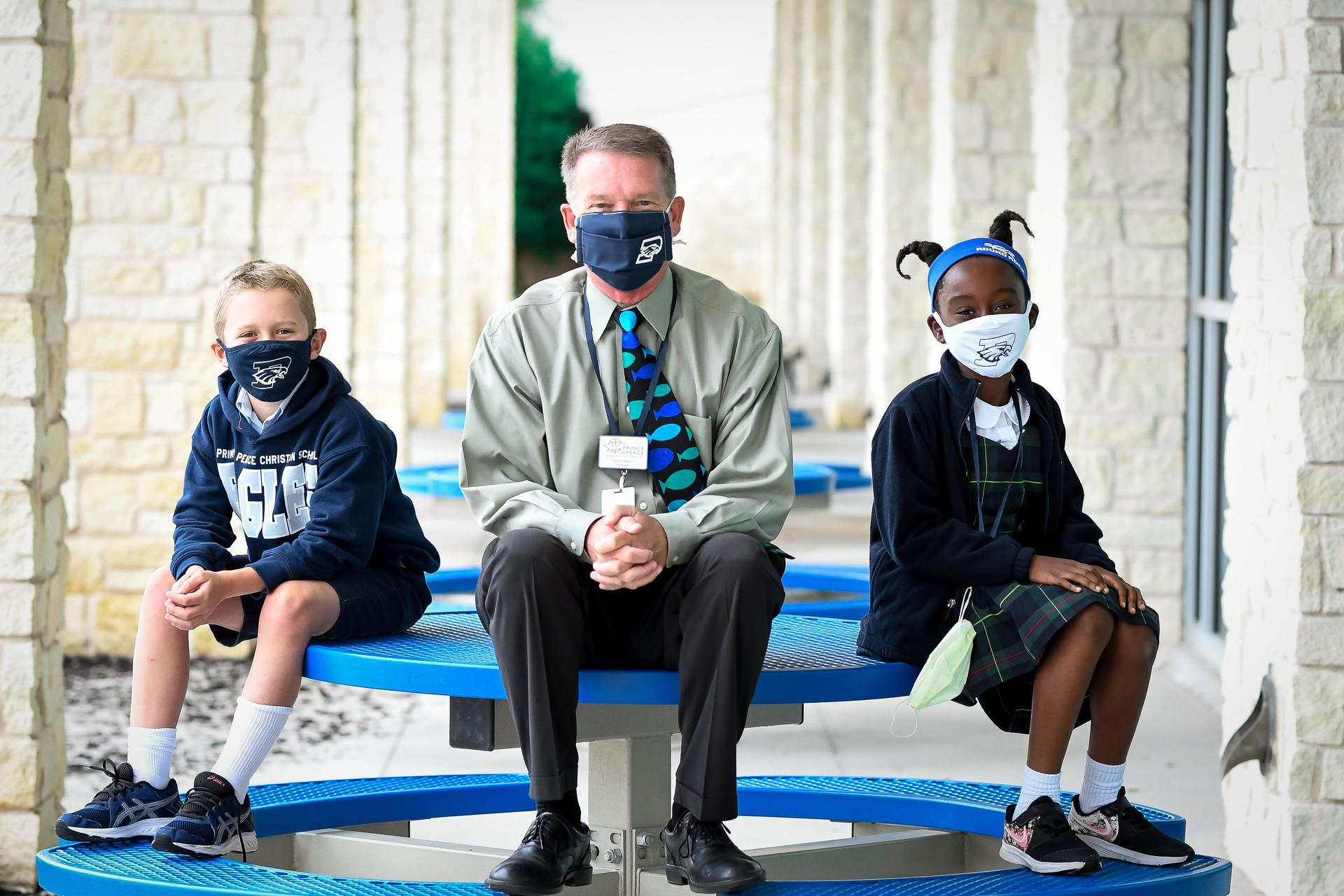headmaster and kids with face masks