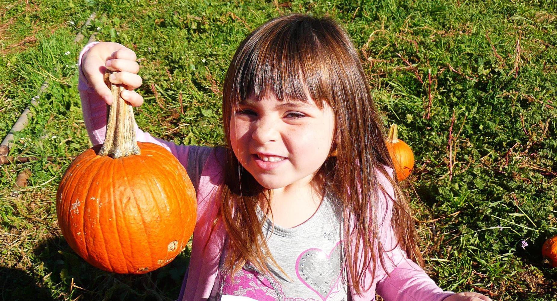 Student holding up a pumpkin