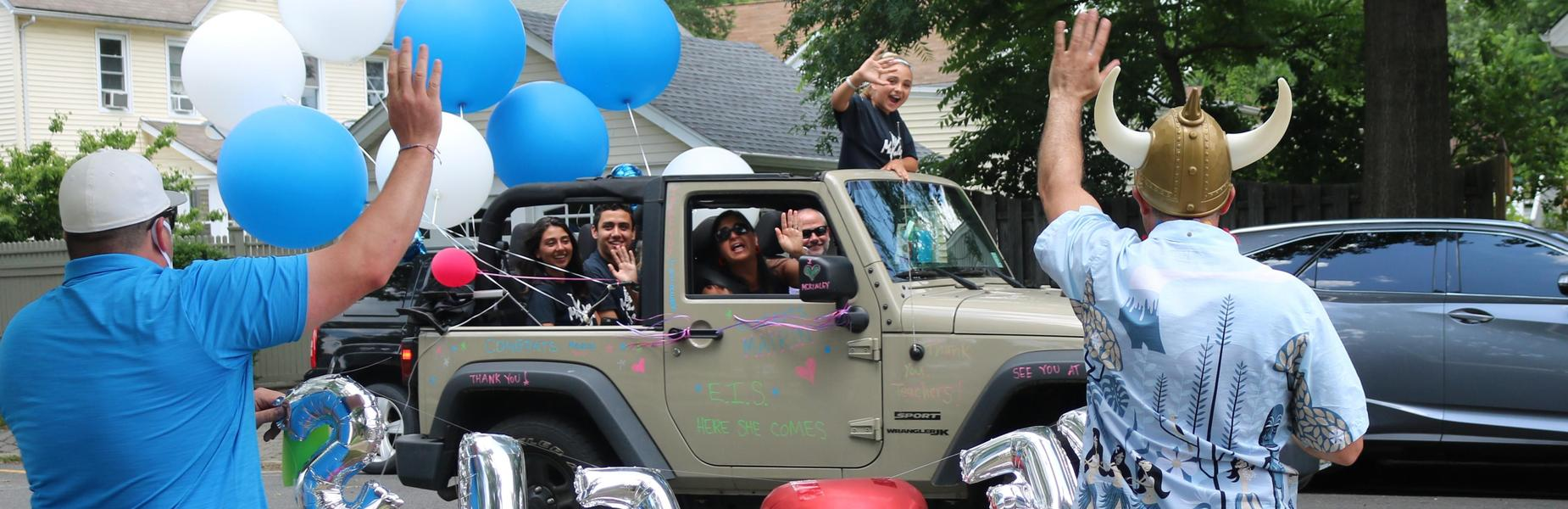 Photo of McKinley 5th grader and family waving to 5th grade teachers during Grade 5 Clap Out Car Parade.