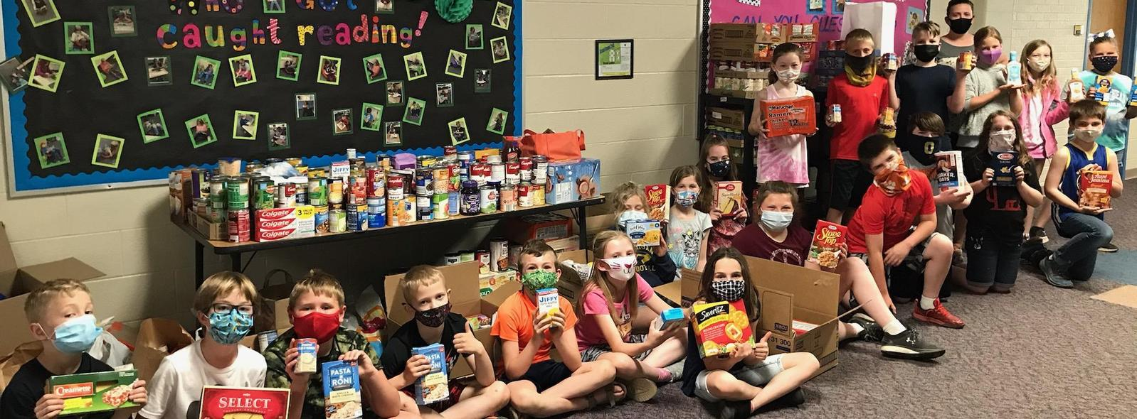 class of students by food drive table