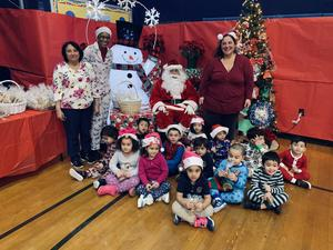 Santa seated with a class of students wearing their pj's