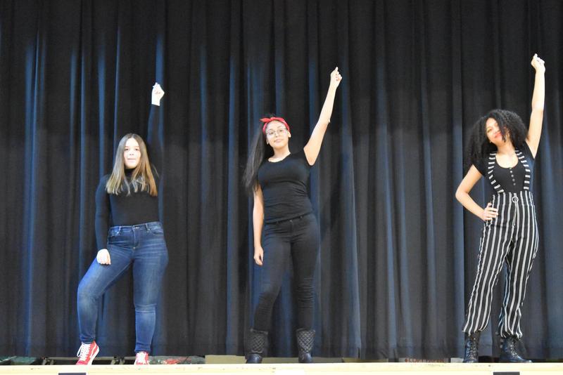 Three girls in black on stage