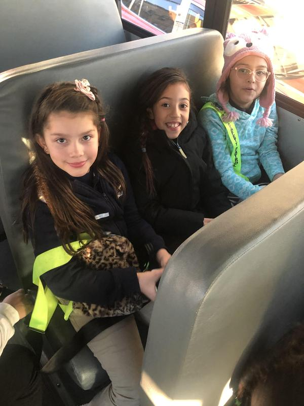 three safety patrol girls seated next to each other on the bus
