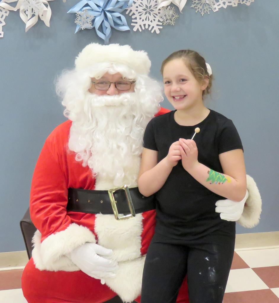 A girl smiles widely as she visits with Santa