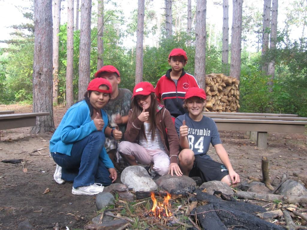 kids with their thumbs up, celebrating the building of a fire