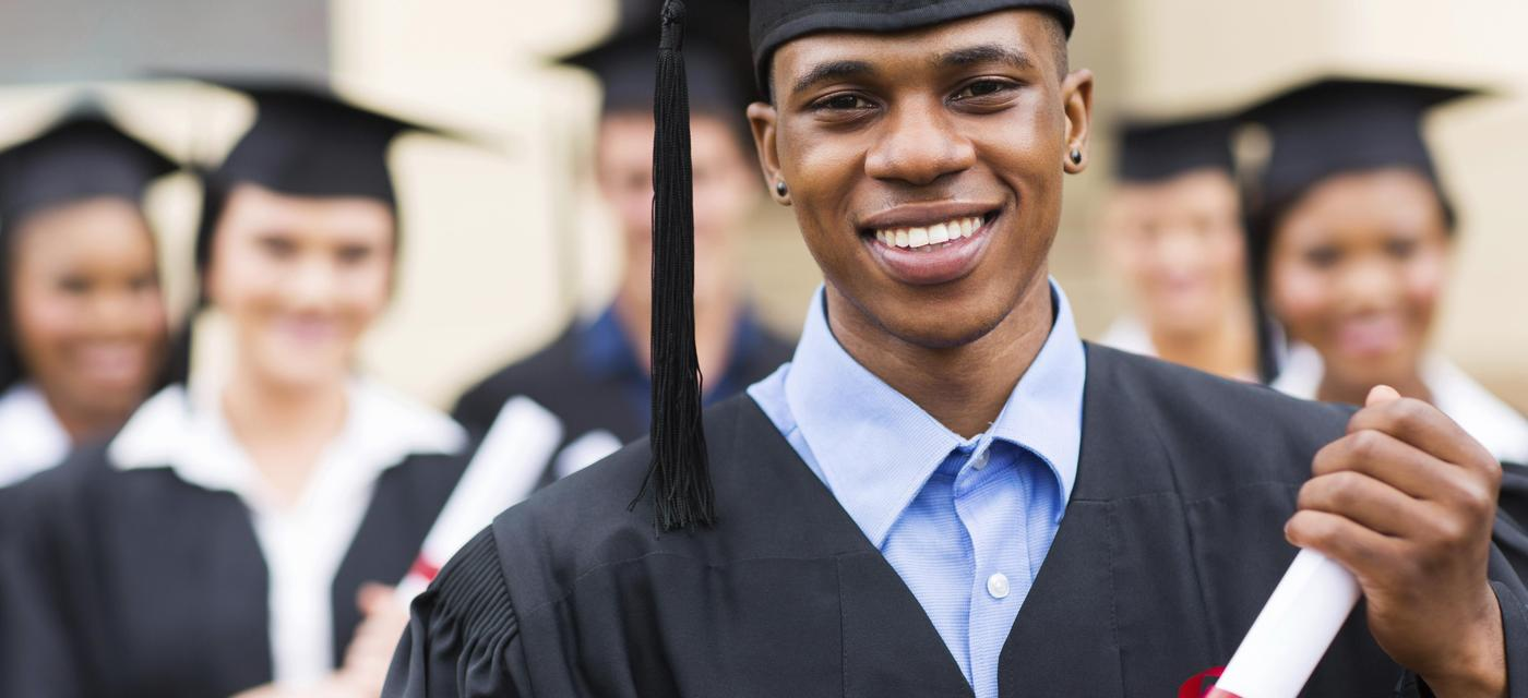 students in caps and gowns with diplomas