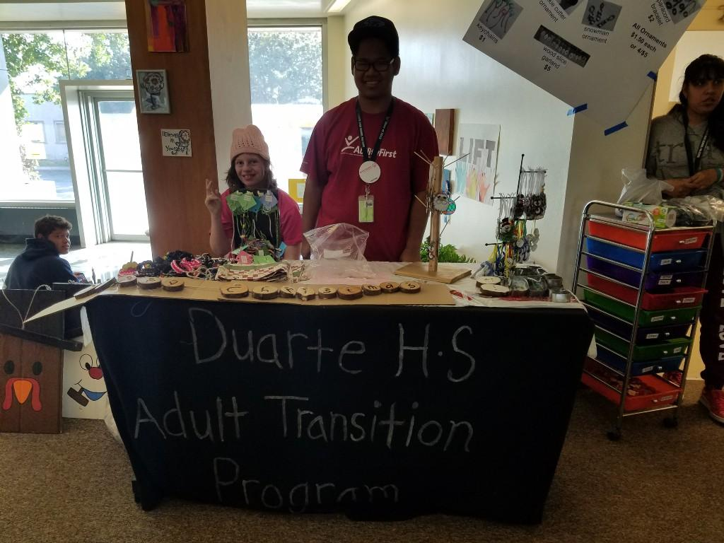 Students standing at table selling crafts