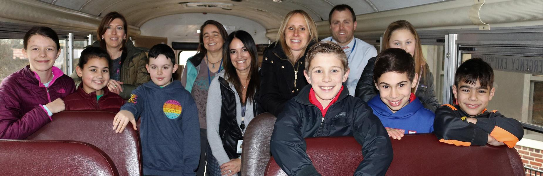 Photo of Franklin students and staff aboard a bus filled with donated toys to be delivered to charitable organization in Newark.