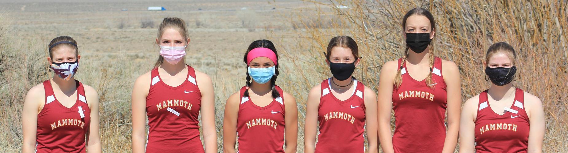 Girls cross country team lined up with masks