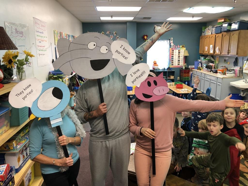 Teachers hold up homemade masks of popular children's characters.