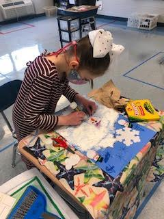 A young student works on an art project on a desk