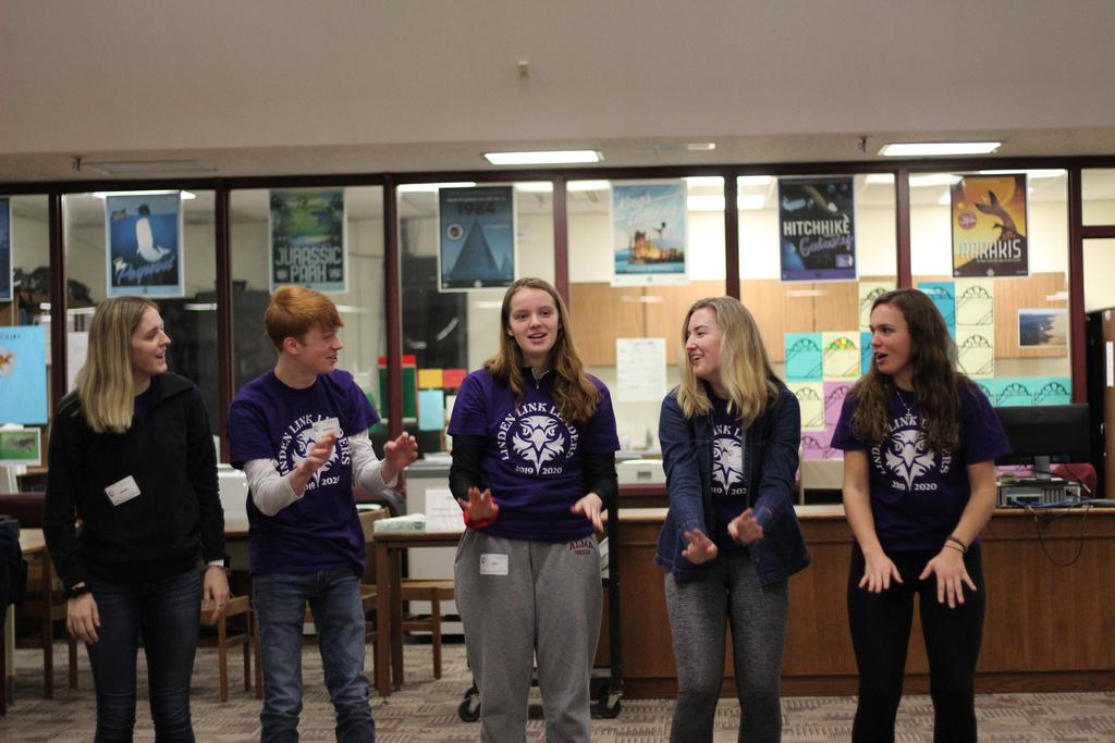 Students wearing purple t-shirts and standing in a line.